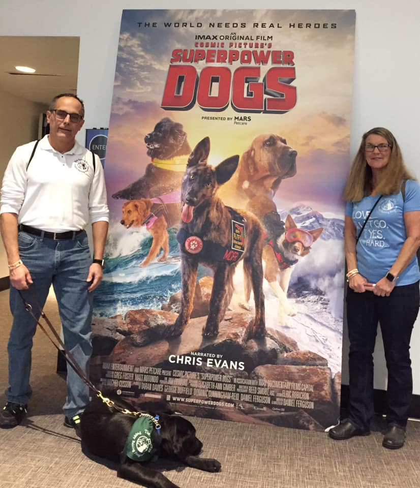 Dogs standing in front of Superhero Dogs movie poster