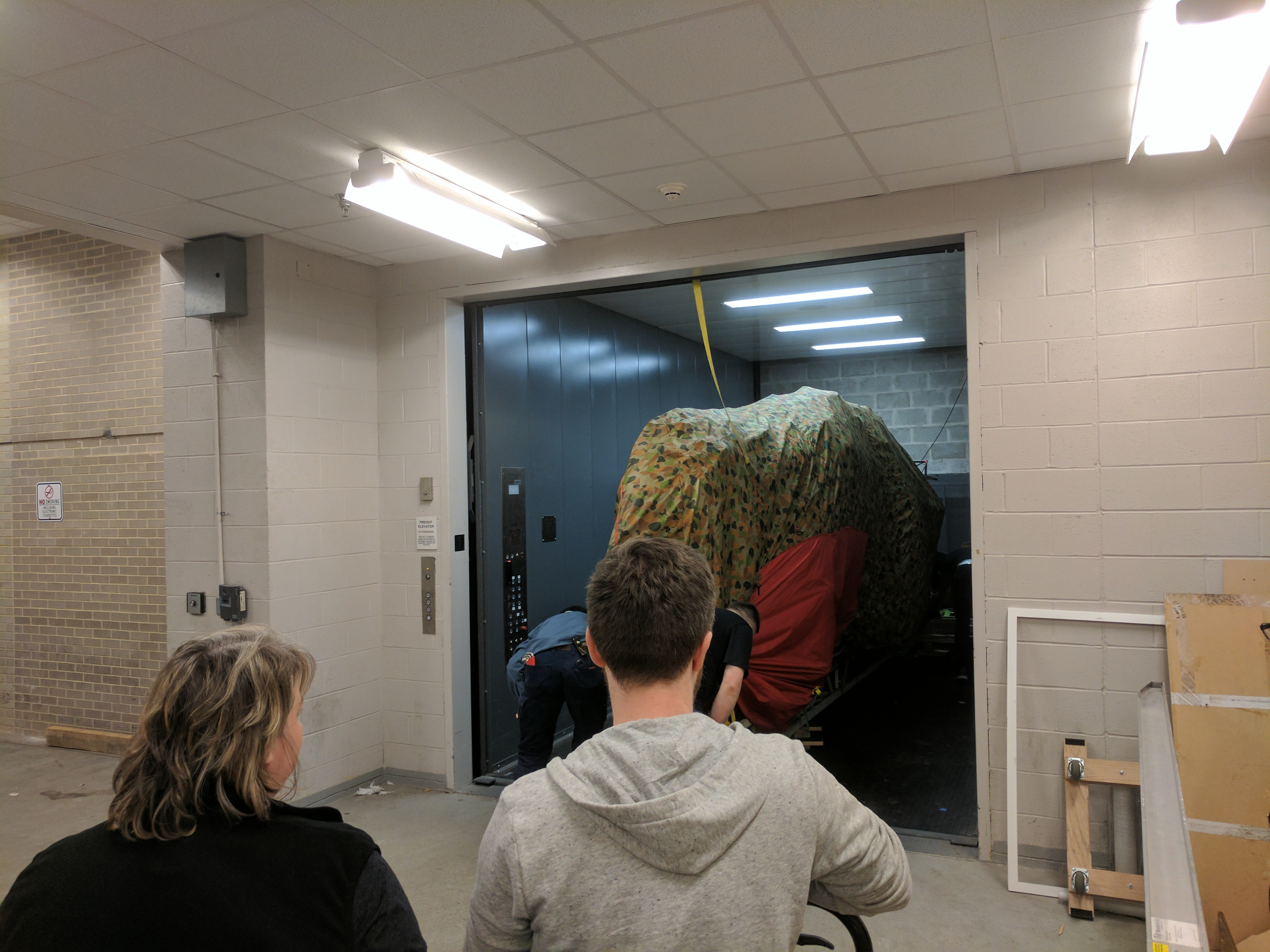 Photograph of a dinosaur model being transported in an elevator for the Jurassic World exhibit in 2016