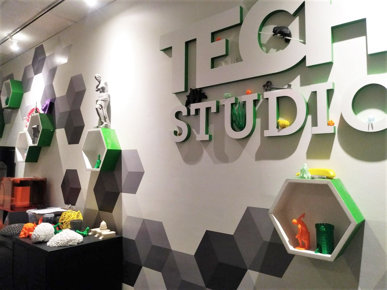 "A wall at The Franklin Institute is decorated with hexagons and 3D printed objects and bears the label, ""Tech Studio."""