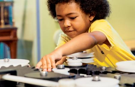 A young boy reaches for gear in the permanent Franklin Insitute exhibit, Amazing Machine.
