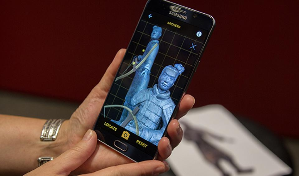 A phone displays 3D models of the Standing and Kneeling Archers, two statues found with the ancient Terracotta Army.