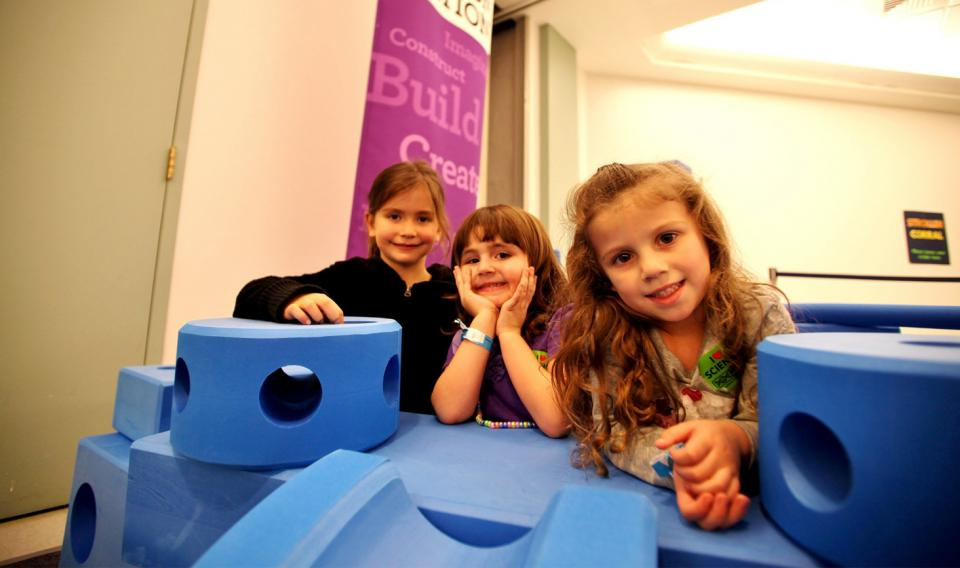 Girls playing with Giant Tinker Toys at the Institute's Creation Station in 2012