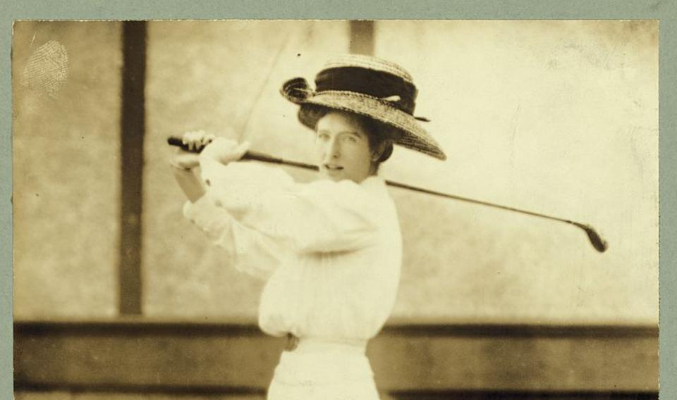 A woman swinging a golf club.