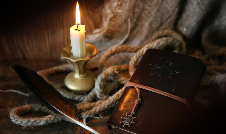 Image of lit candle and brass candle holder, rope, and old notebook