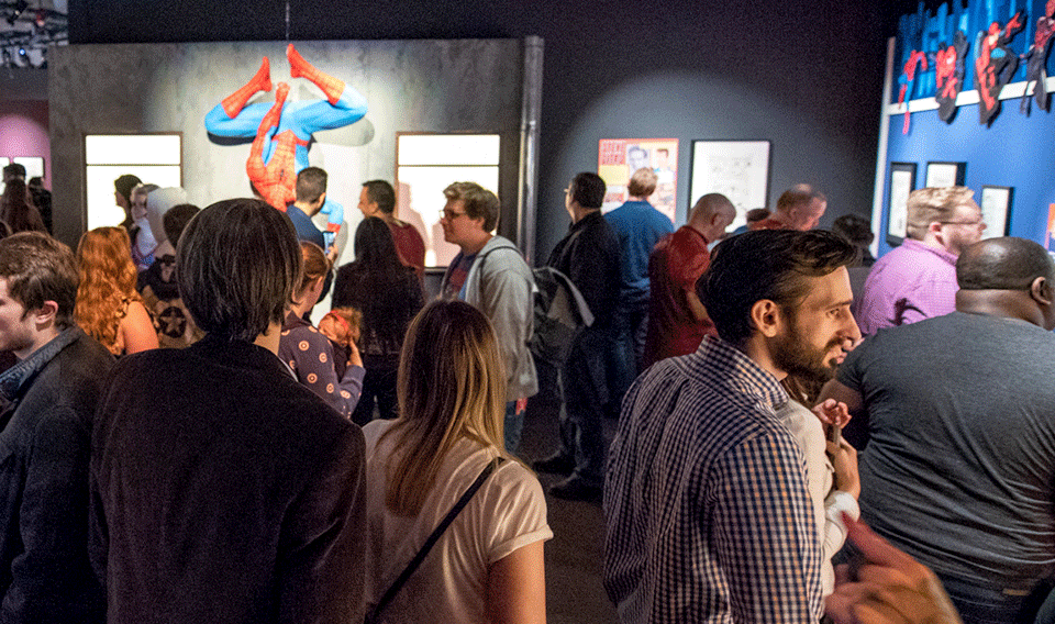 Photograph of a crowd of people viewing the Marvel: Universe of Super Heroes exhibit.