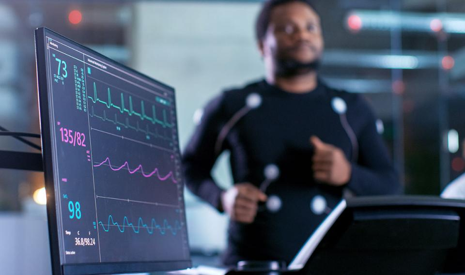 Runner on treadmill with electrodes hooked up to monitor