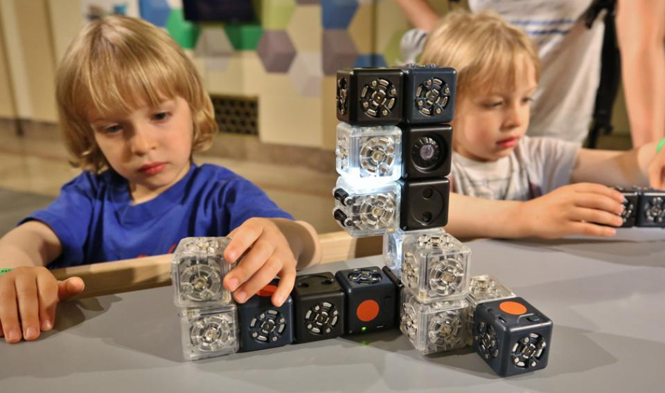 A boy constructs a robot out of Cubelets robot blocks