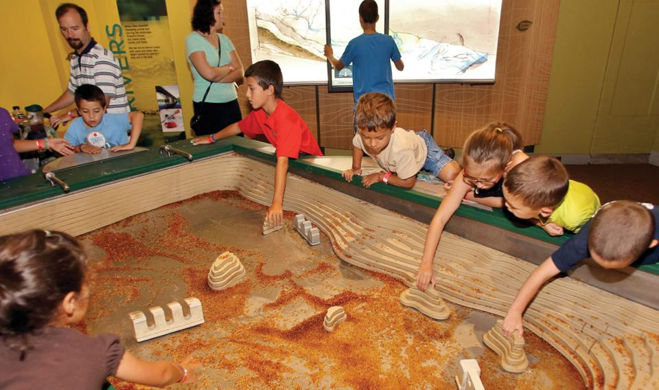 Children learning from the Stream table in Changing Earth at The Franklin Institute.