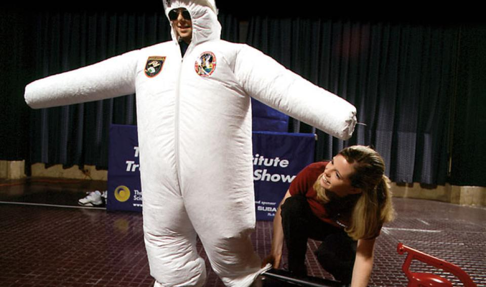 A Franklin Institute Traveling Science Show host wearing an inflatable space suit.