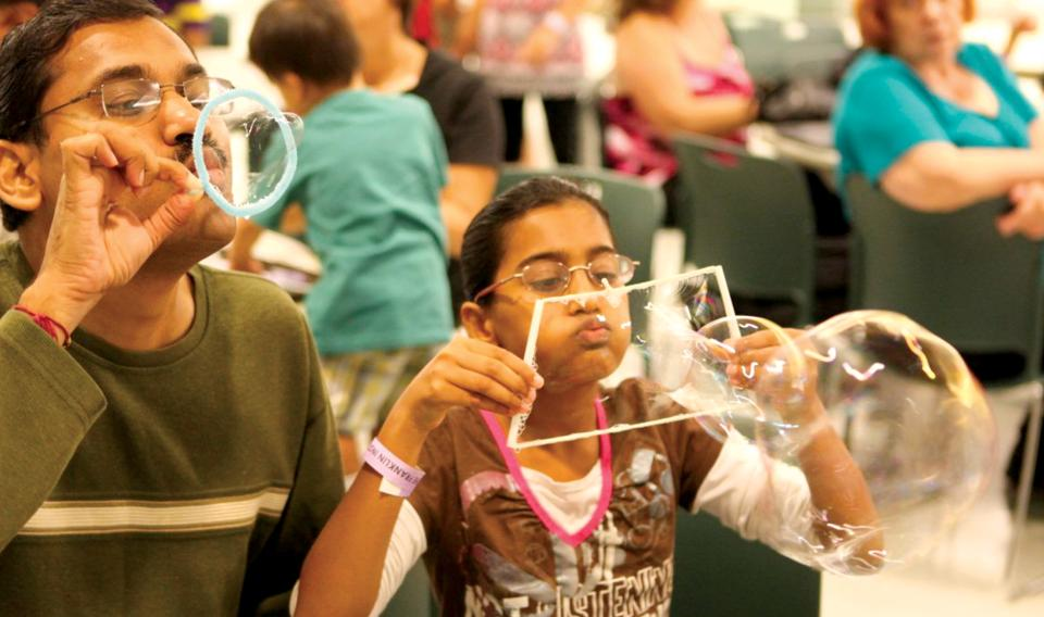 Image of a child blowing bubbles at a science activity