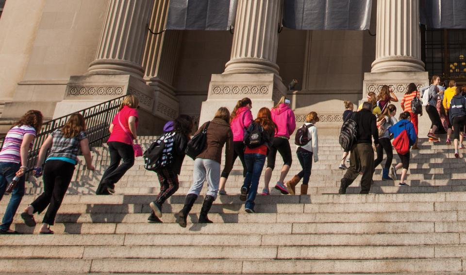 Kids on a field trip walking up the front steps of The Franklin Institute.