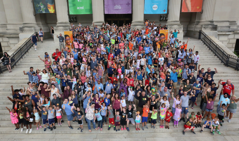 Photograph of families and children on The Franklin Institute stairs in front of the museum