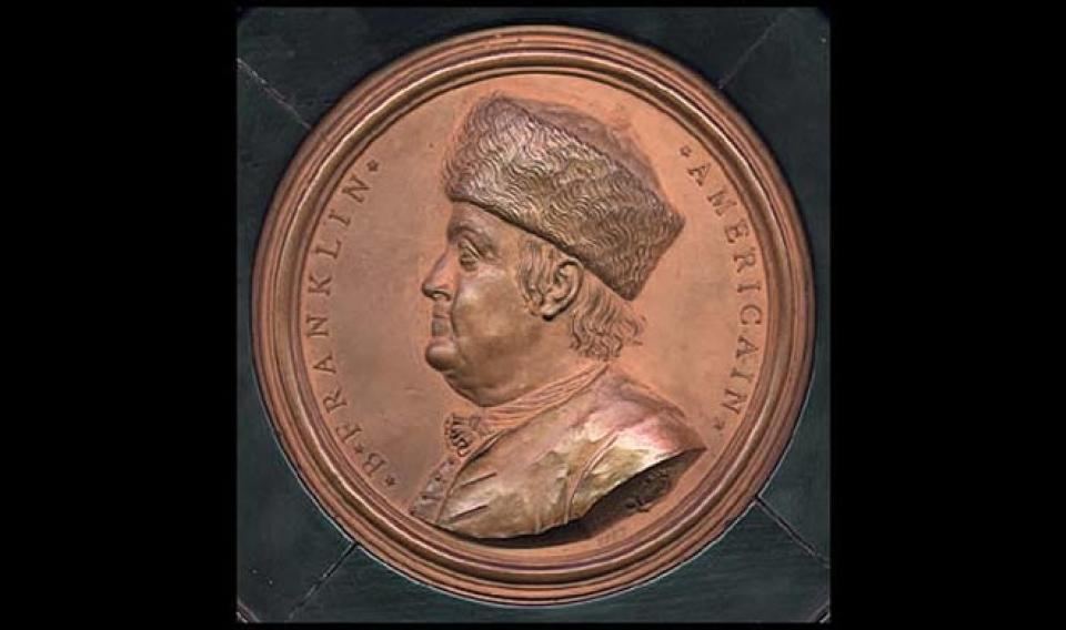 Round Nini Medallion featuring a profile of Benjamin Franklin wearing his famous fur hat