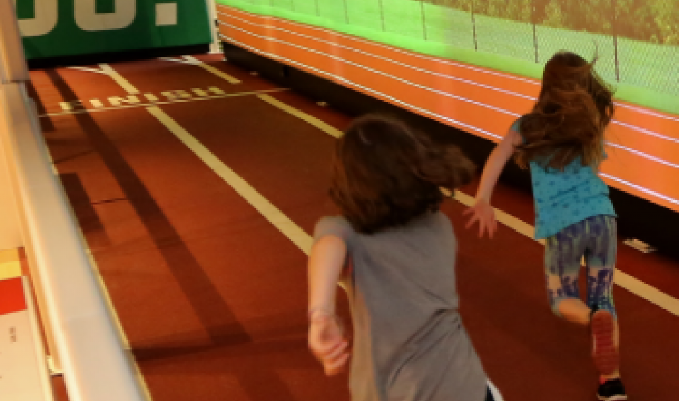 Two children run on the race track in the Sports Zone exhibit at The Franklin Institute.