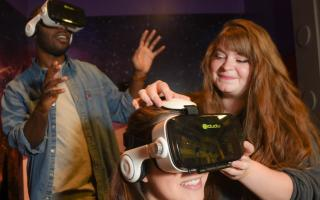 Museum staff member helping guests experience virtual reality through a headset at the Franklin Instutute