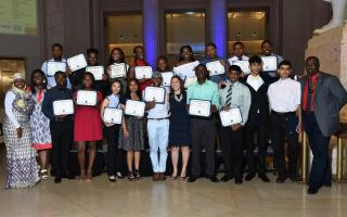 Group photo of youth program students holding diplomas at graduation