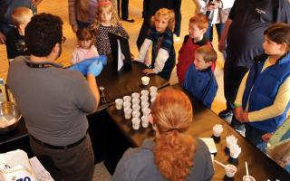 Kids gathered around a table with cups learning about food science