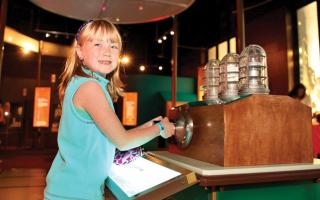 A girl generating power to light a lightbulb at the Franklin Institute.