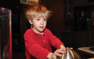 A boy is touching a sphere giving off static electricity, causing his hair to stand on end at the Franklin Institute.