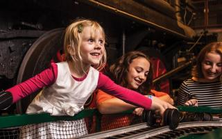 A young girl learning how the wheels on a train track work in the Train Factory exhibit at The Franklin Institute.