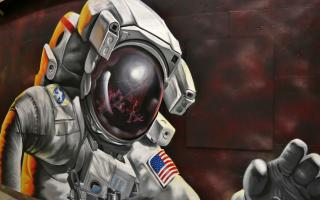 """Reflections of Greatness"" mural of an Astronaut in space, with ISS reflected and Earth in the background."
