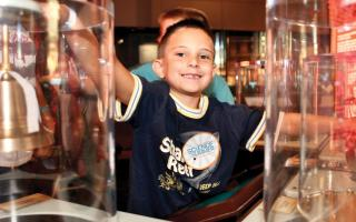 A Young boy is smiling at the camera while enjoying the permanent exhibit, Electricity