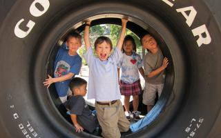 Kids having a great time outside during Discovery Camp inside a giant tire.