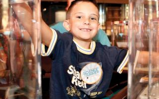 A young boy is smiling at the camera while enjoying the permanent exhibit, Electricity, at The Franklin Insitute.