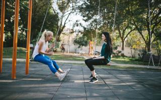 two young women sitting on swings
