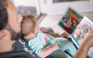 father reading story to his baby