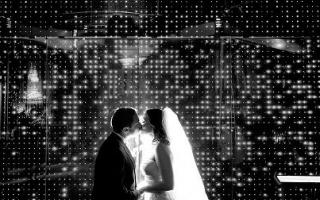 Newlyweds kissing in front of the Electricity Wall at the Franklin Institute.