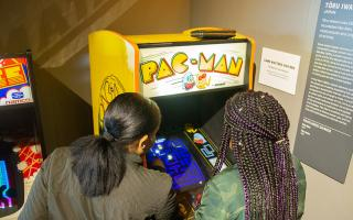 Two Women Playing Pac Mac Arcade Game