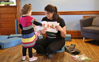 Photo of Franklin Institute's Tara Cox reading a storybook to a young child.