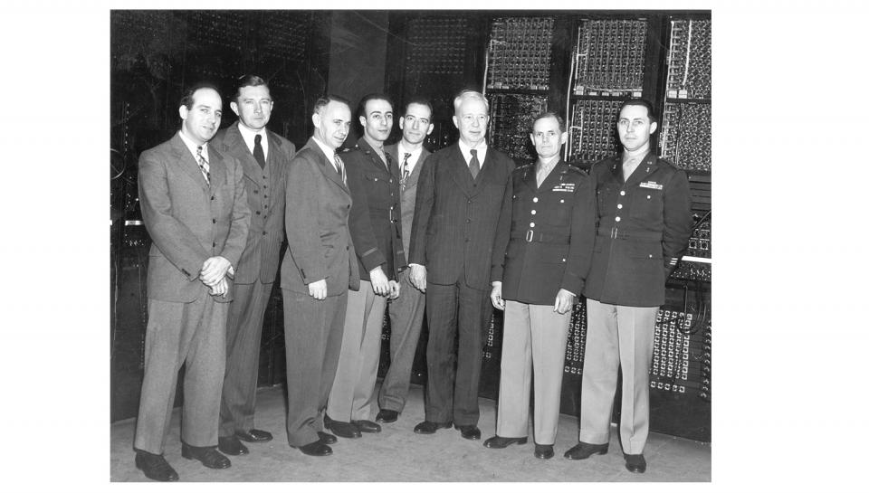 ENIAC engineers and army officials standing in front of the ENIAC.