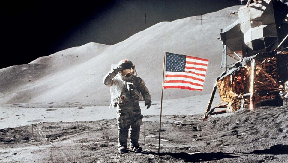 Astronaut David Scott gives salute beside U.S. flag during EVA