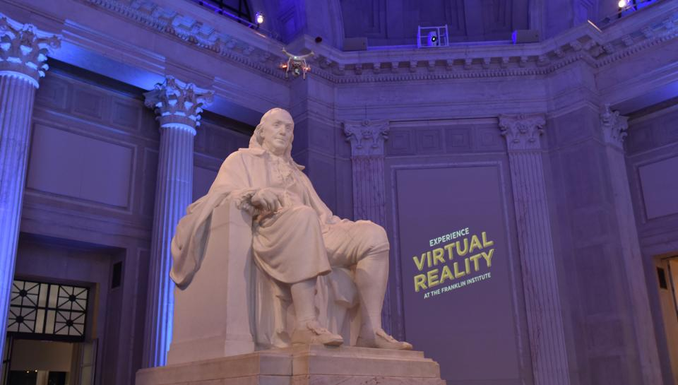 "The Benjamin Franklin Memorial sculpture next to a screen that reads: ""Experience Virtual Reality at The Franklin Institute"""