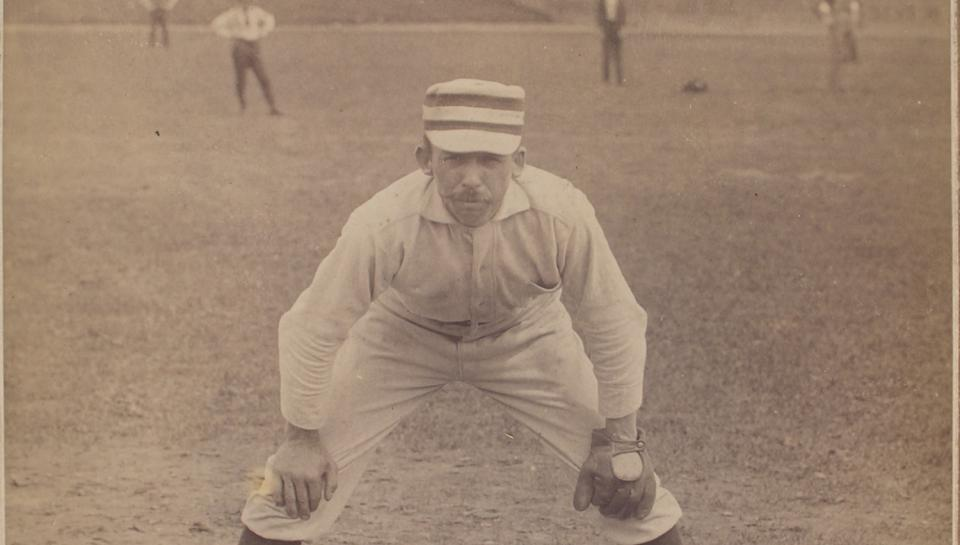 A baseball player in a stance to catch the ball.