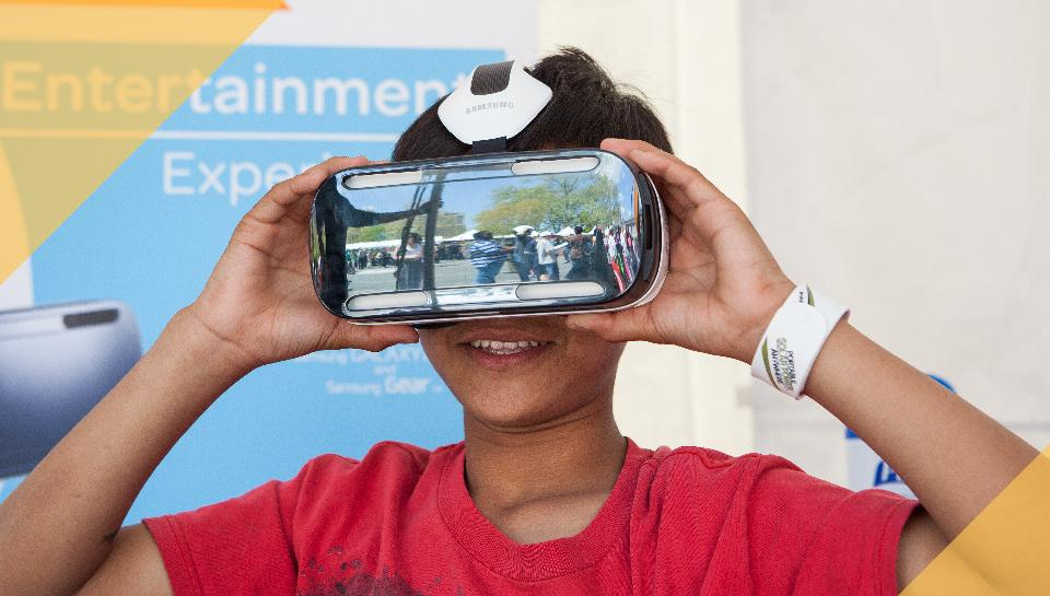 Photo of a kid trying a VR headset an exhibit booth at the Philadelphia Science Festival Carnival