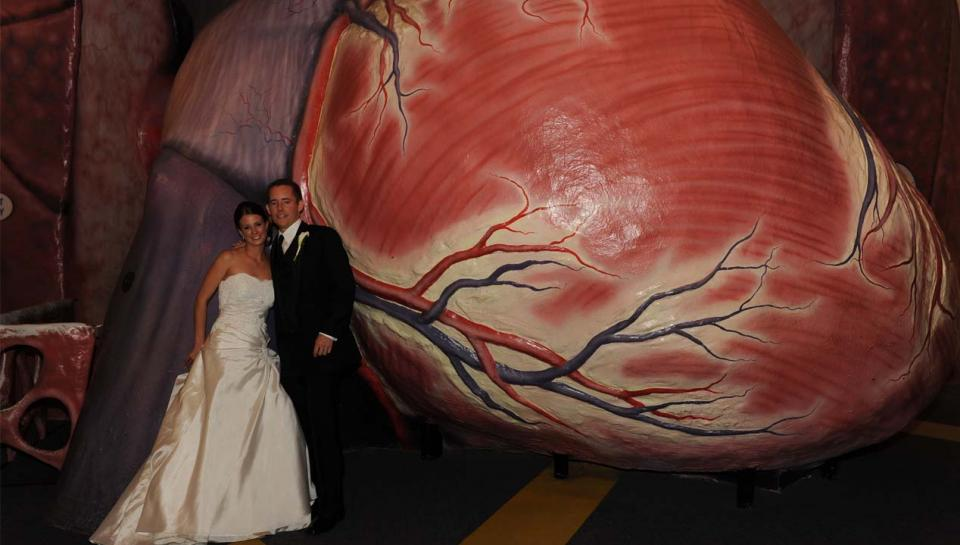 A newlywed couple in from of The Giant Heart at the Franklin Institute.
