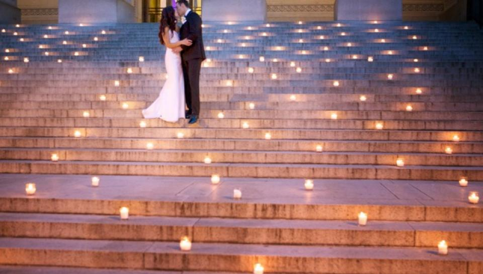 Newlyweds kissing on the steps to The Franklin Institute.