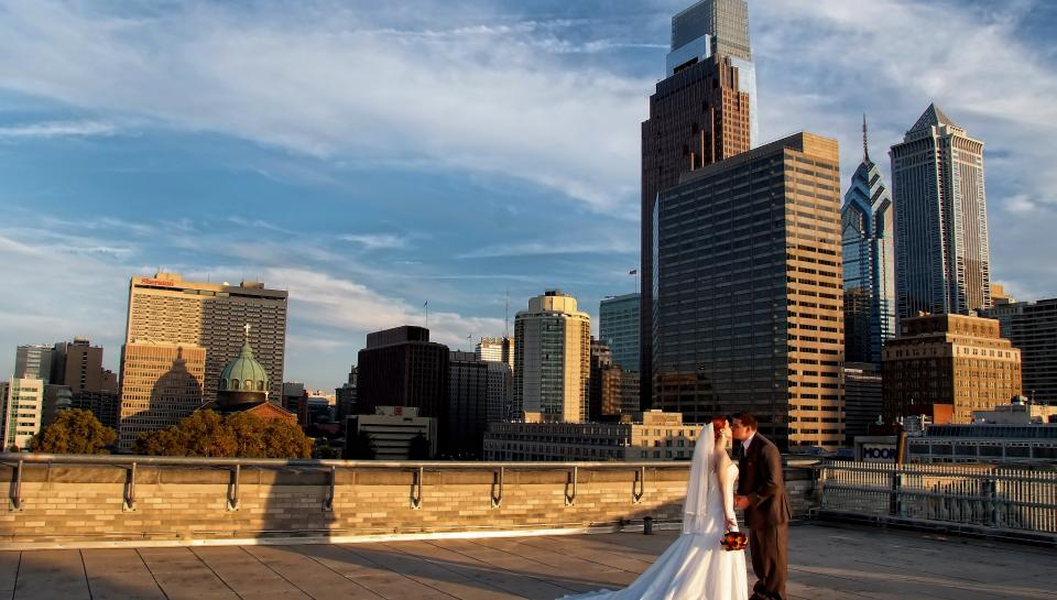 Newlyweds kissing on the roof of The Franklin Institute.