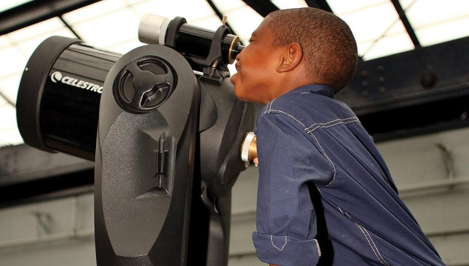 A young boy learns about astronomy while using a Celestron telescope at the Institute.