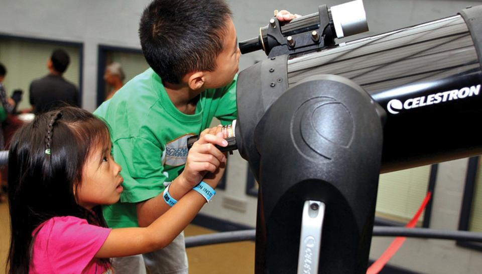 Two young children looking through a telescope in the Observatory.