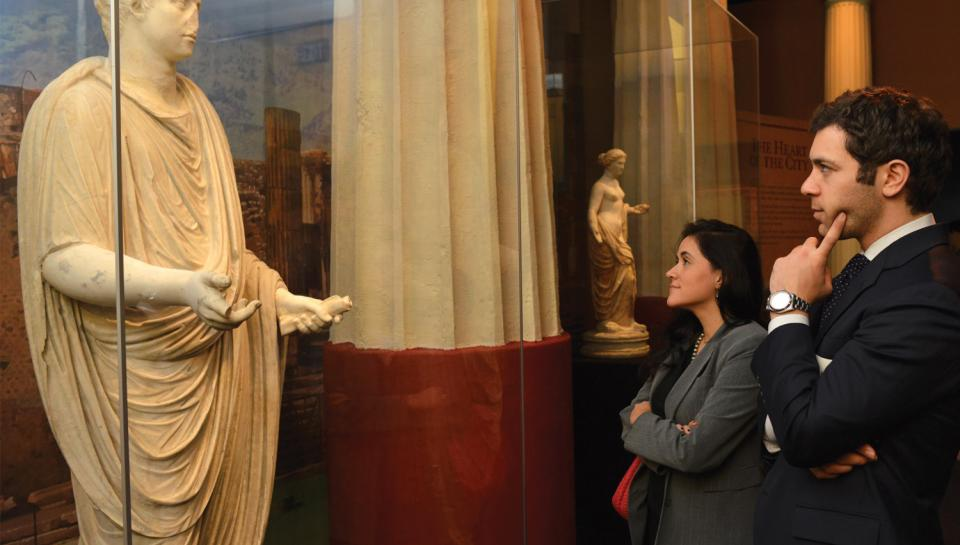 Guests appreciating a statue in the One Day in Pompeii traveling exhibit at The Franklin Institute.