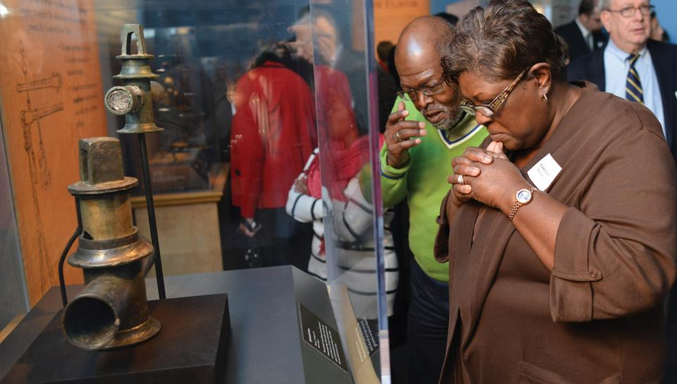 Guests observing a metal object in the One Day in Pompeii traveling exhibit at The Franklin Institute.