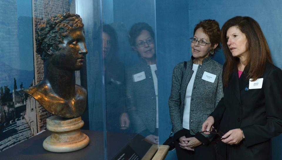 Guests inspecting a metal bust in the One Day in Pompeii traveling exhibit at The Franklin Institute.