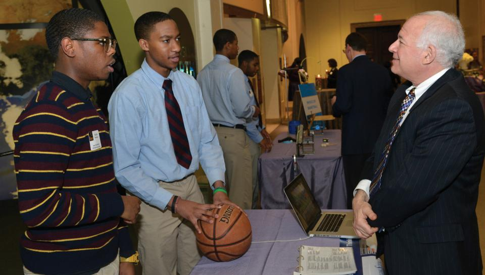 Two Franklin Institute STEM Scholars educating a guest during a STEM Showcase event.