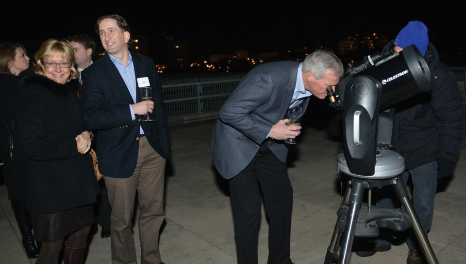 Guests looking through a telescope during a Night Skies event at The Franklin Institute.