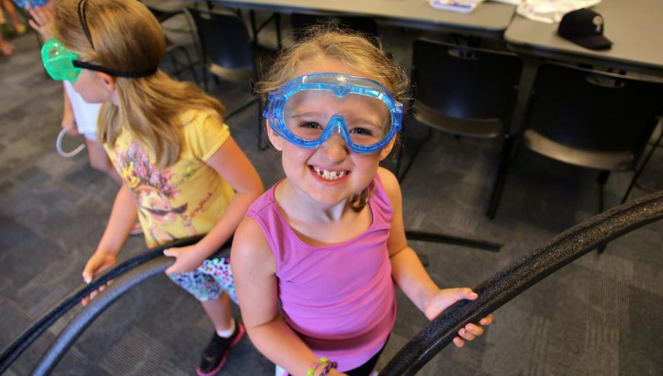 Young Girl wearing goggles during GSK's Science in the Summer.