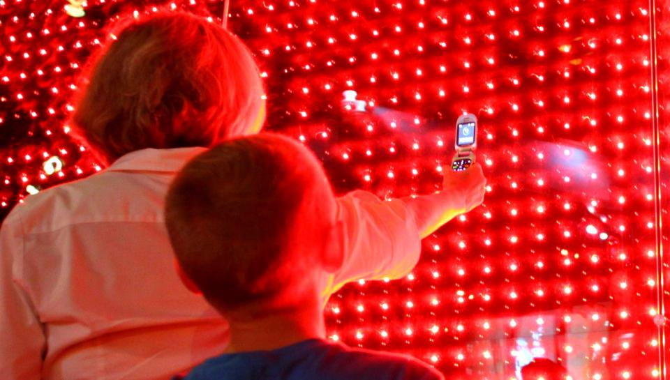 people look at the cell phone wall in the Electricity exhibit